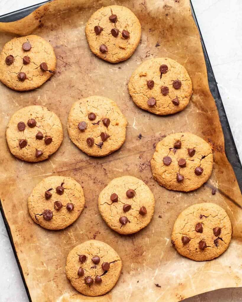 Peanut butter chickpea cookies on a black tray lined with parchment paper.