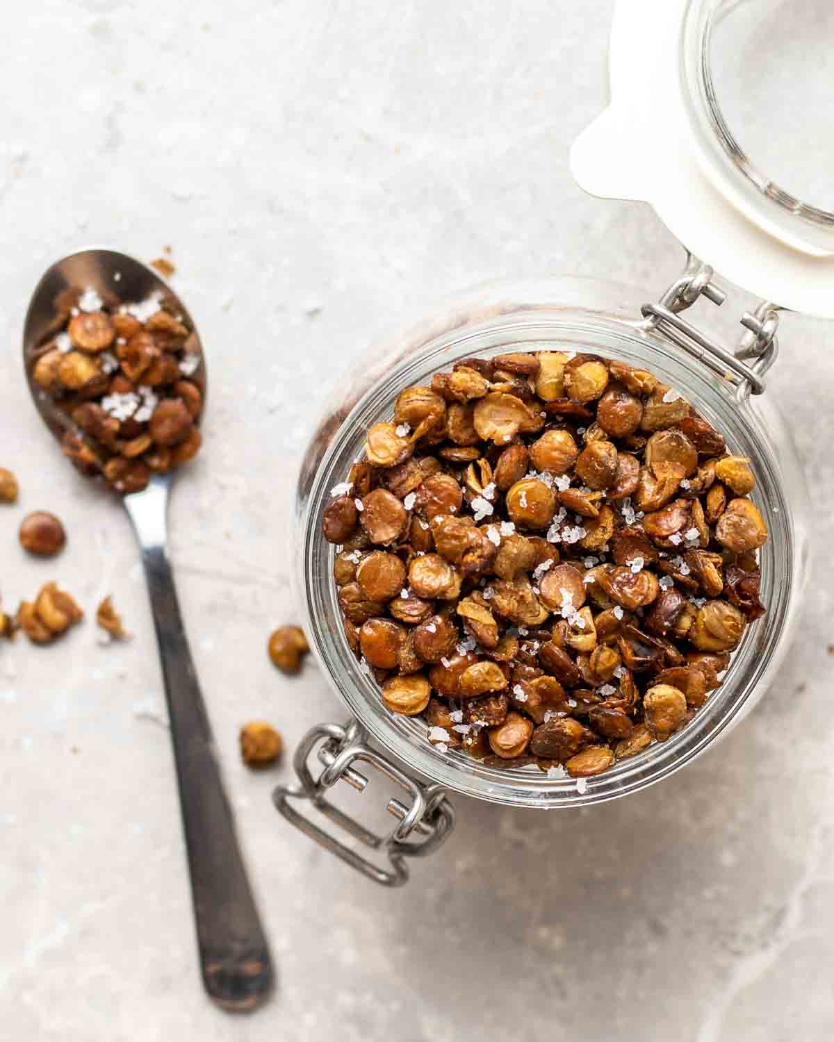 Roasted lentils in a small jar. There is a spoon with lentils in the background.