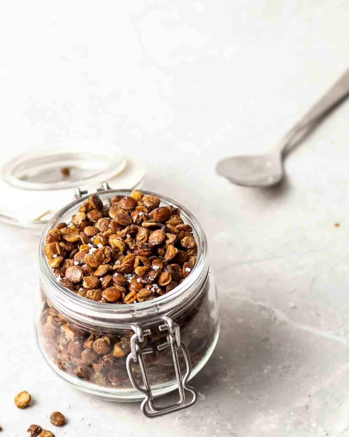 Roasted lentils in a small glass jar. There is a teaspoon in the background.