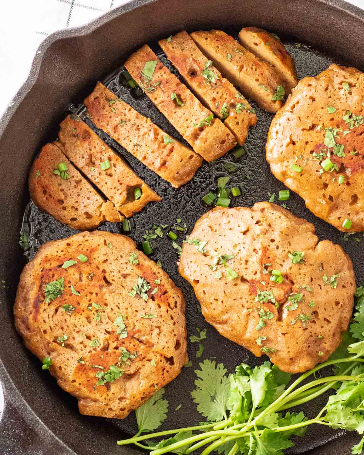A few pieces of seitan chicken in a black pan with one of it being sliced into pieces. They are topped with chopped cilantro.
