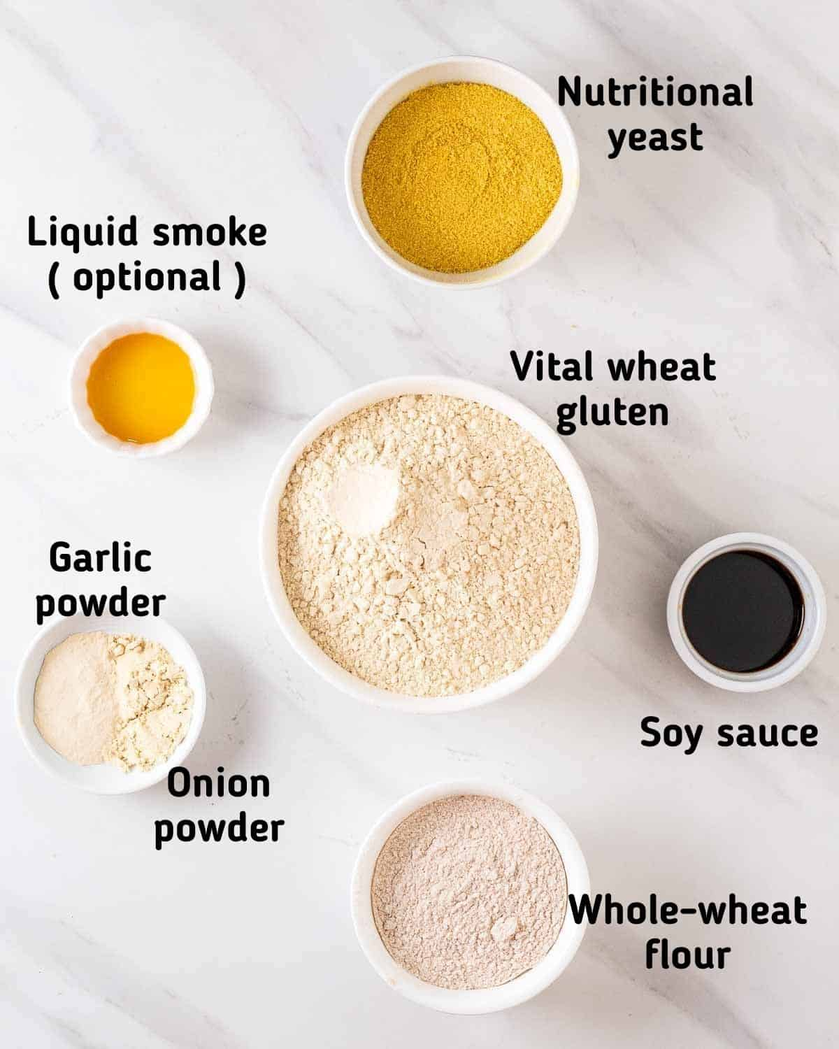 Ingredients needed to make this recipe like nutritional yeast, liquid smoke, vital wheat gluten, whole wheat flour, soy sauce, garlic and onion powder arranged on a white background.