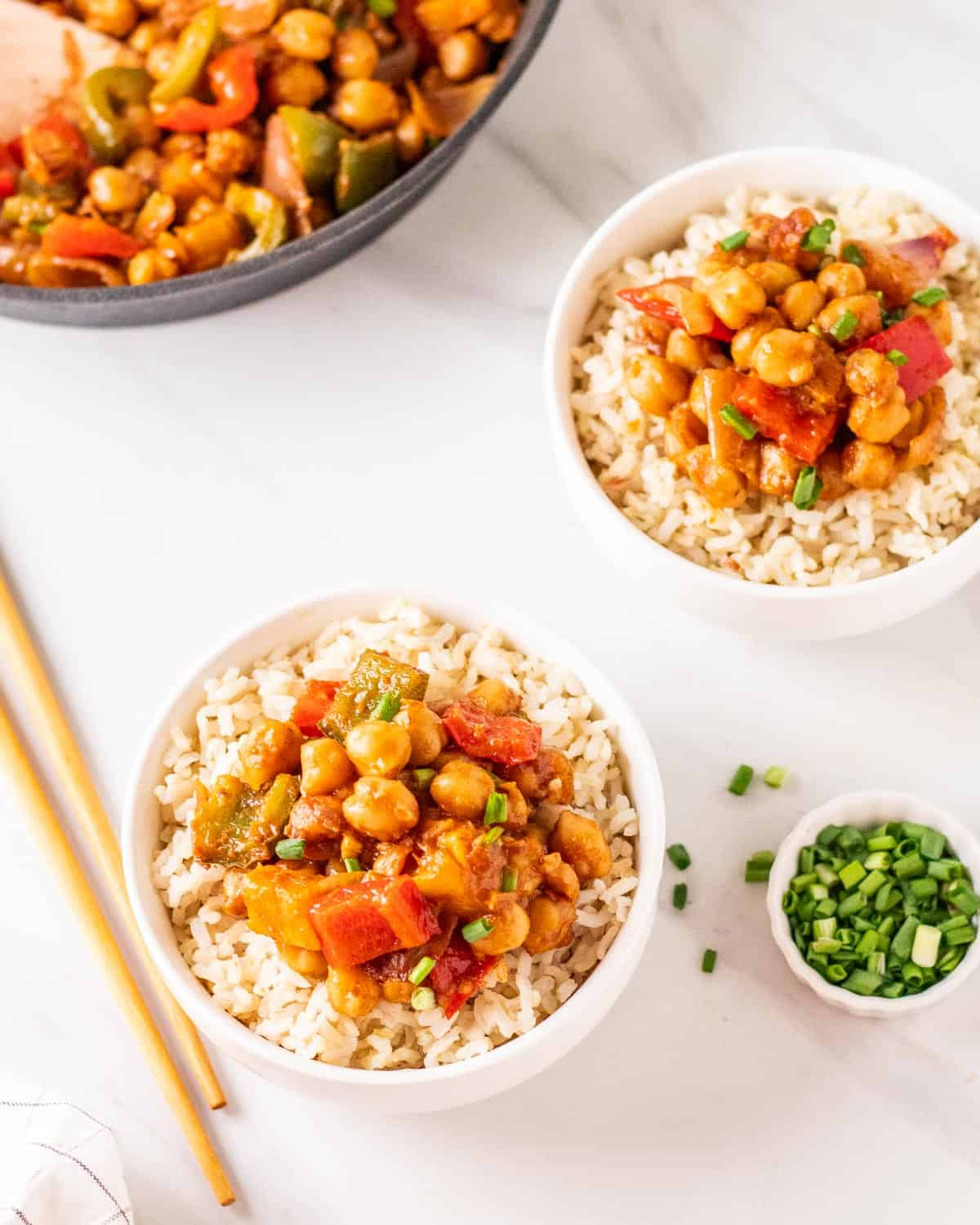 sweet and sour chickpea served on 2 bowls of white rice.
