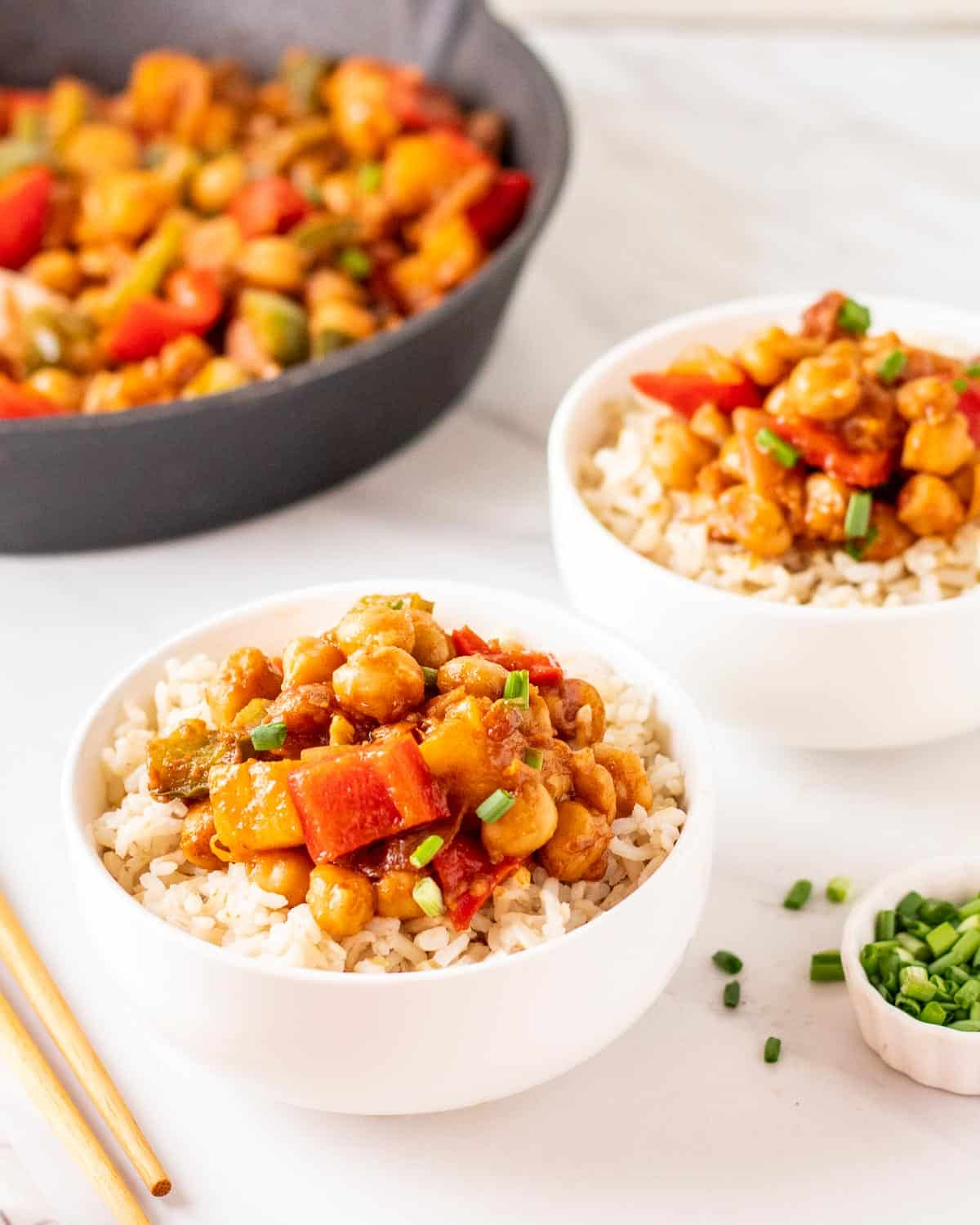 Close up shot of sweet and sour chickpeas served on a bed of brown rice.