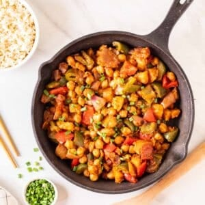 Overhead shot of sweet and sour chickpeas in a black skillet.