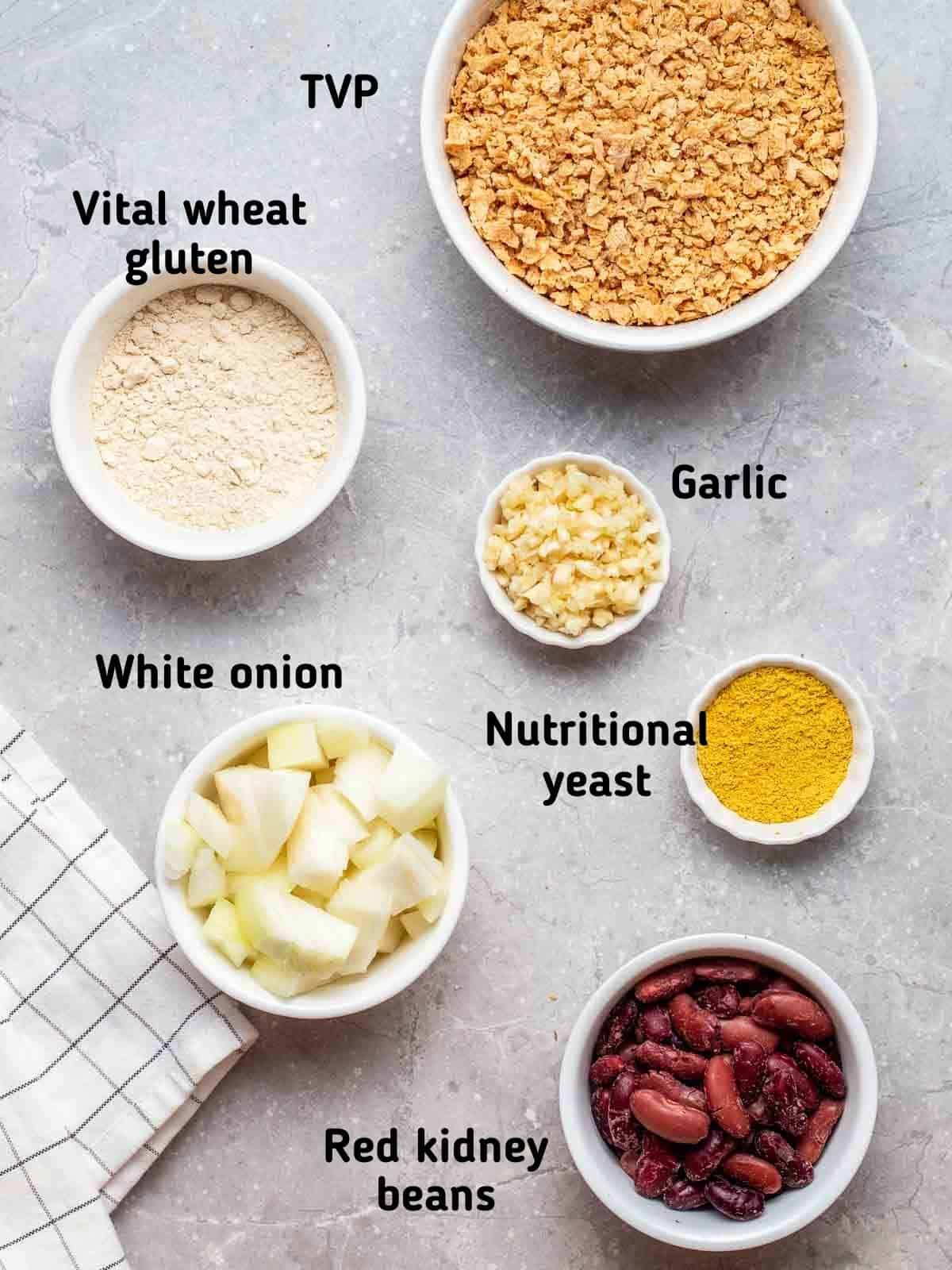 Ingredients needed like TVP, wheat gluten, beans, garlic and onion on a grey background.