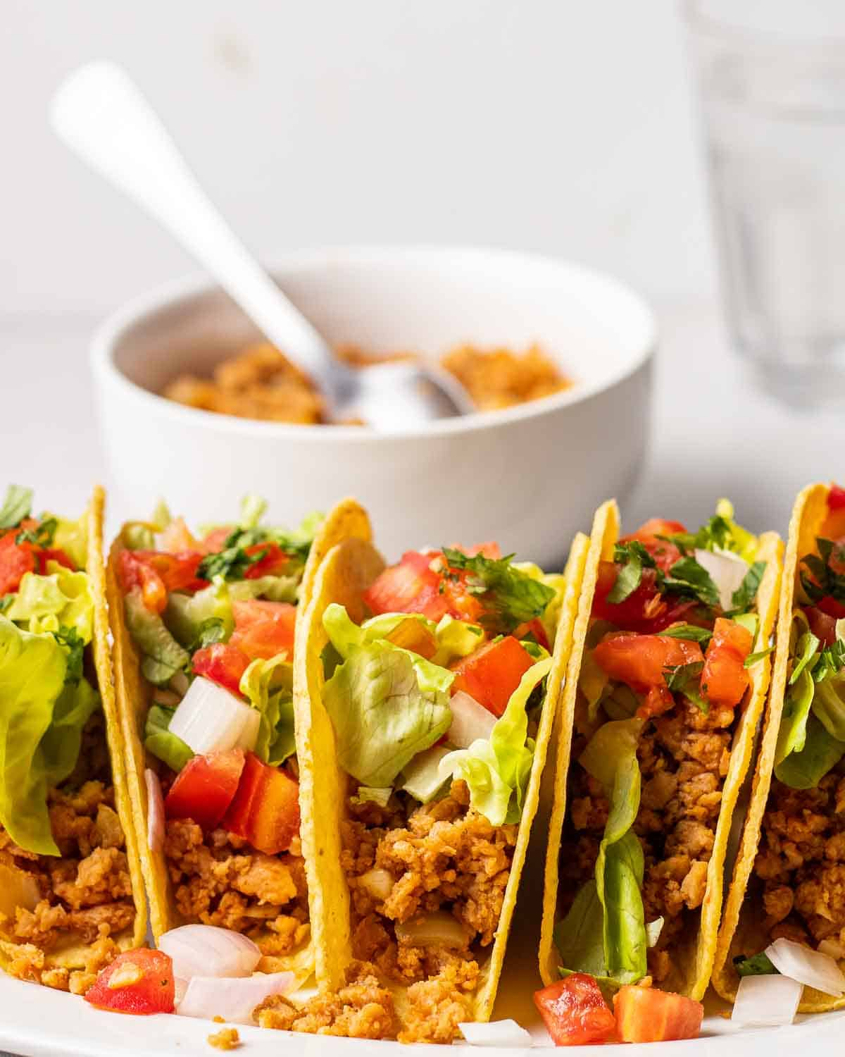 TVP tacos arranged on a plate. There is a bowl of taco meat and glass of water behind.