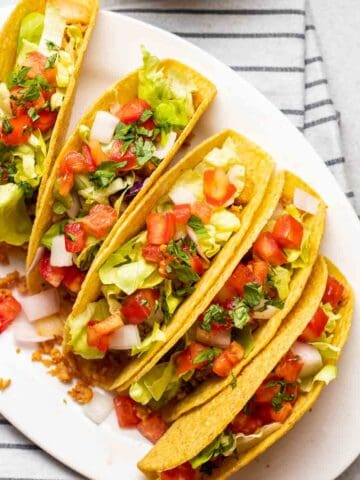 5 tacos arranged on a white oval plate.