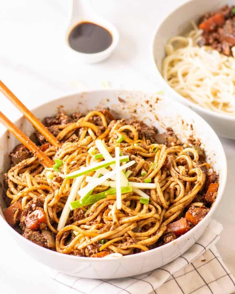 Bowl of noodles with sauce mixed in with chopsticks.