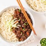 A close up shot of a bowl of jajangmyeon with chopsticks on the side.