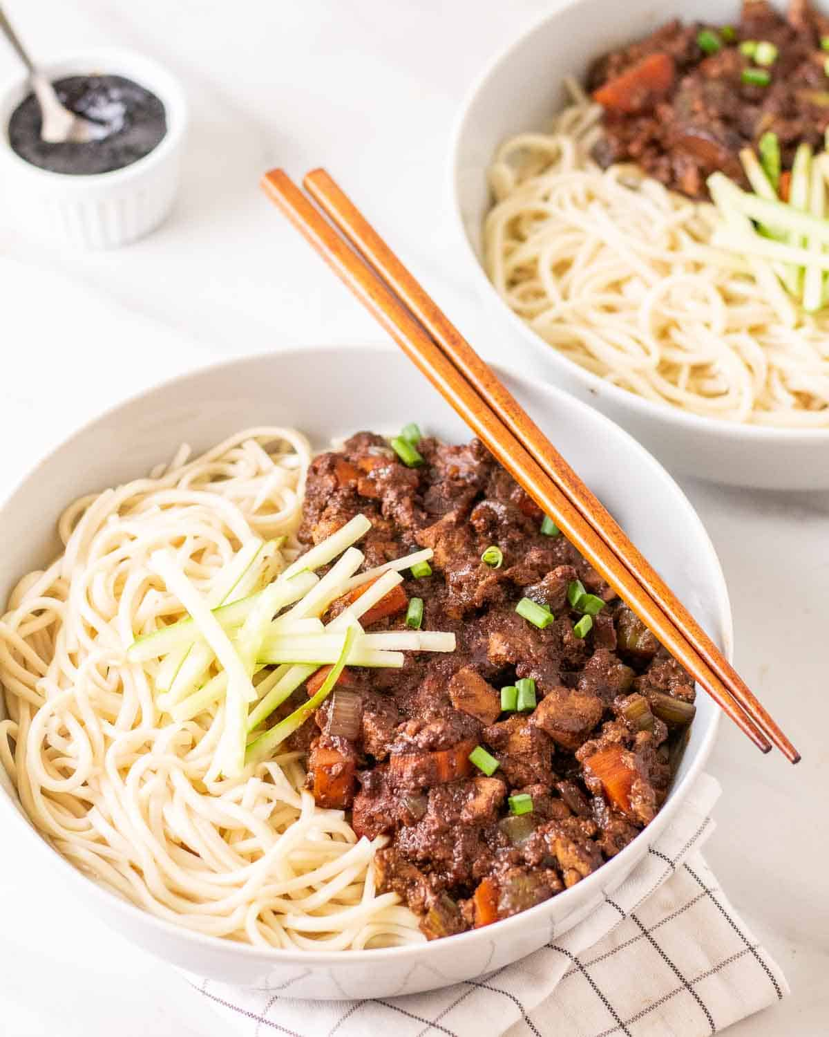 A bowl of vegan jajangmyeon with chopsticks. There is another bowl of noodles and black bean sauce behind.