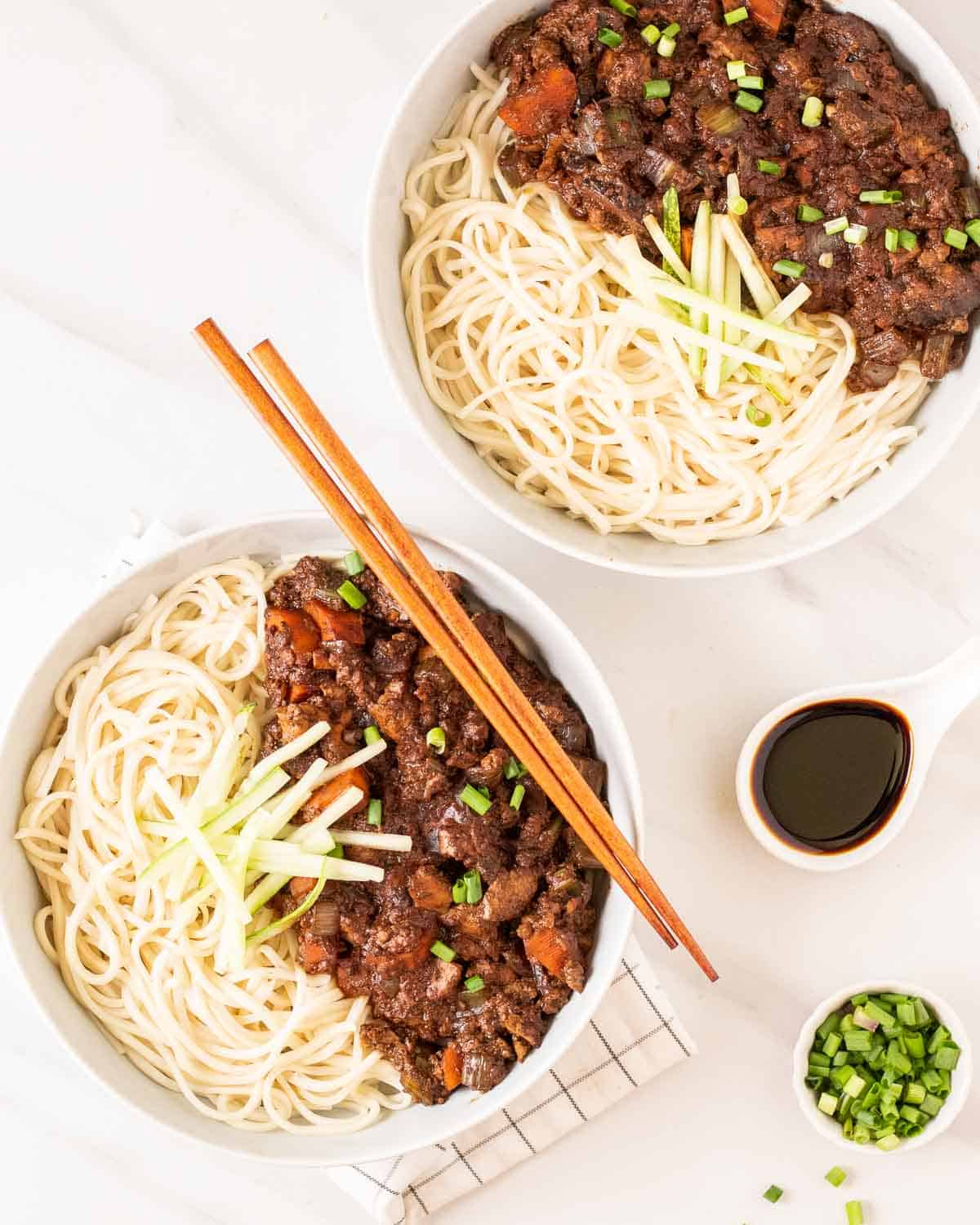 2 bowls of jajangmyeon with chopsticks. There is chopped scallions and soy sauce in the background.