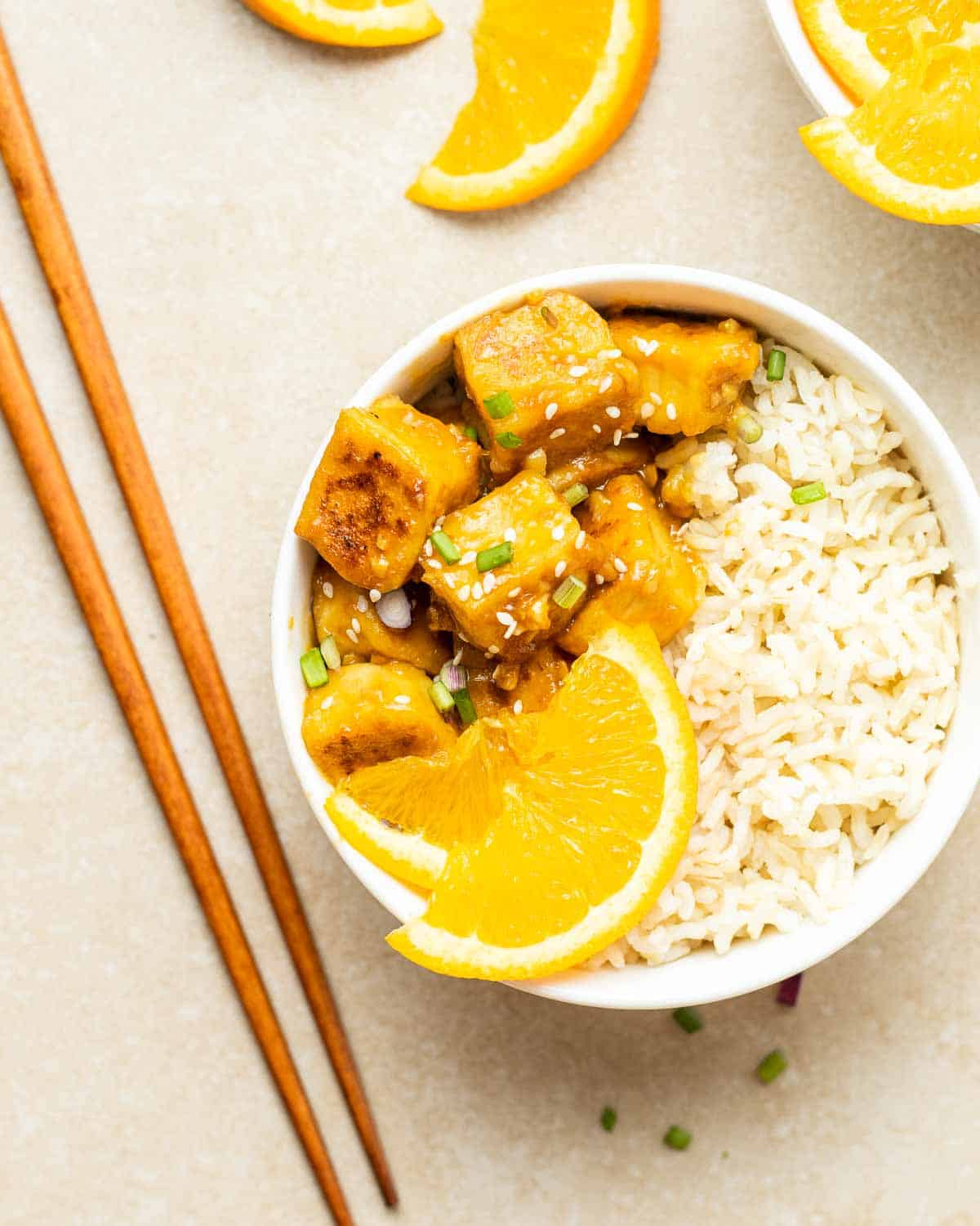 Orange tofu served on a bed of rice topped with scallions and orange slices with chopsticks beside it.