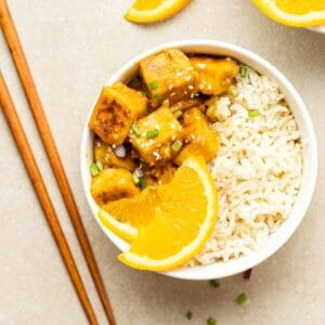 Orange tofu served with brown rice and orange slices in a white bowl with a pair of chopsticks beside.