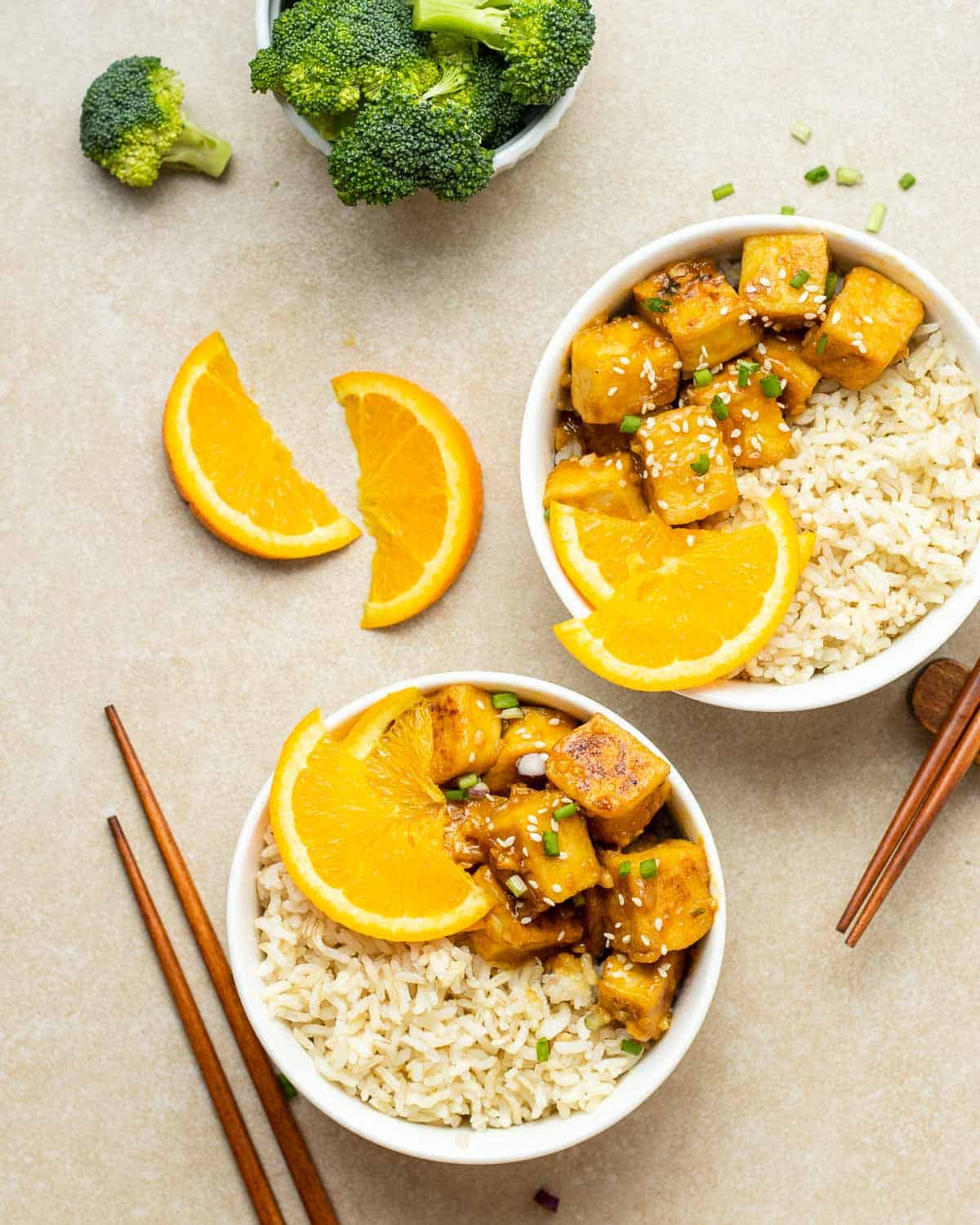 2 bowls of rice served with orange tofu with chopsticks. There is broccoli floret and orange slices in the background.