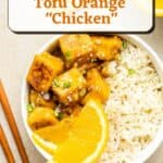 A bowl containing orange tofu and rice topped with orange slices and chopped scallions with text overlay.
