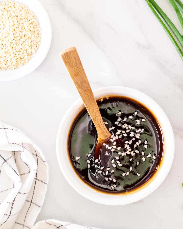 An overhead shot of vegan teriyaki sauce in a ramekin with a wooden spoon.