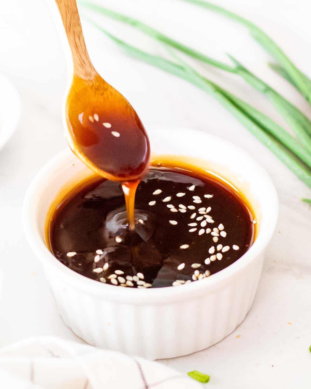 Spooning out a spoonful of teriyaki sauce in a ramekin.