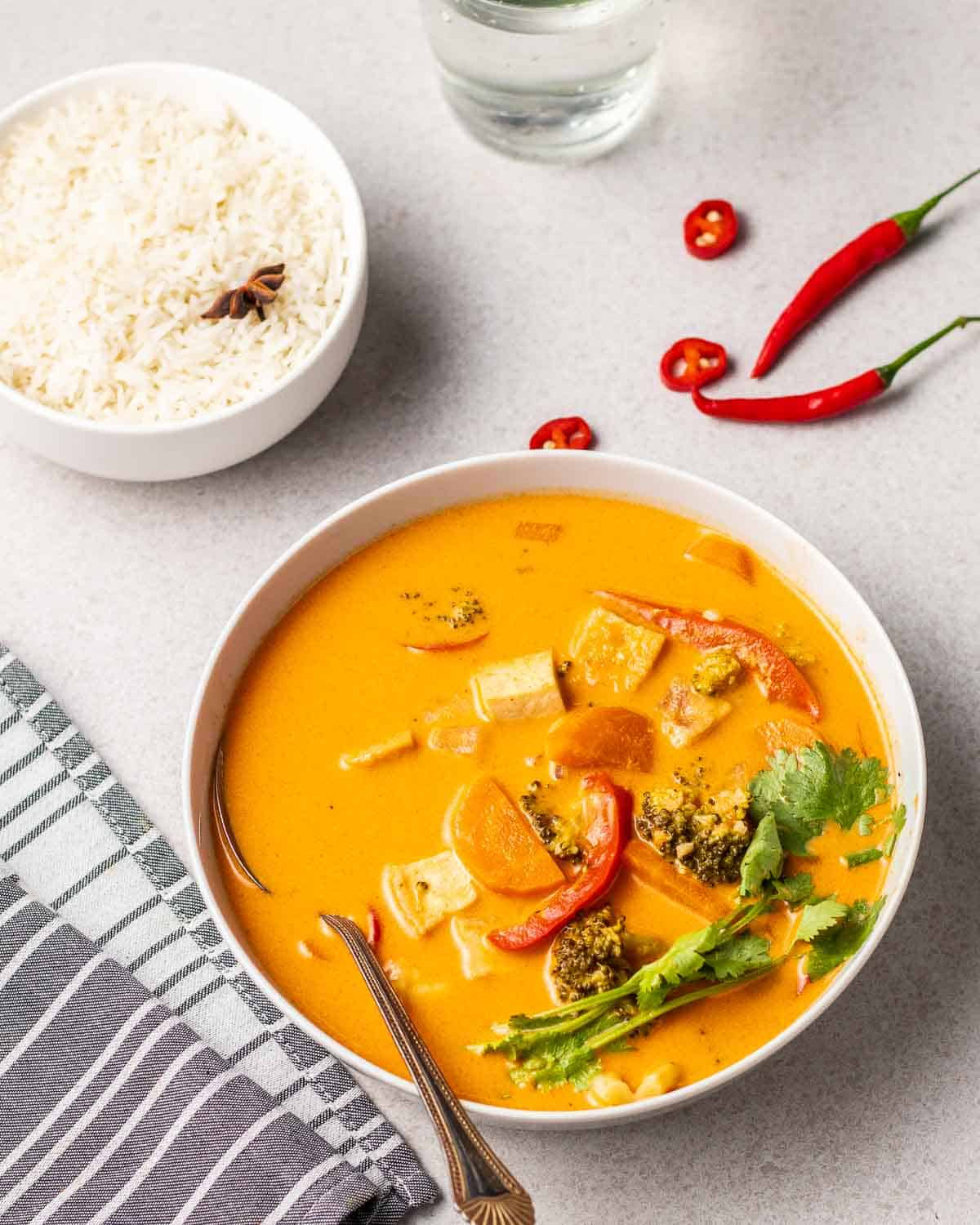 Vegan Thai red curry served in a white bowl with a spoon.