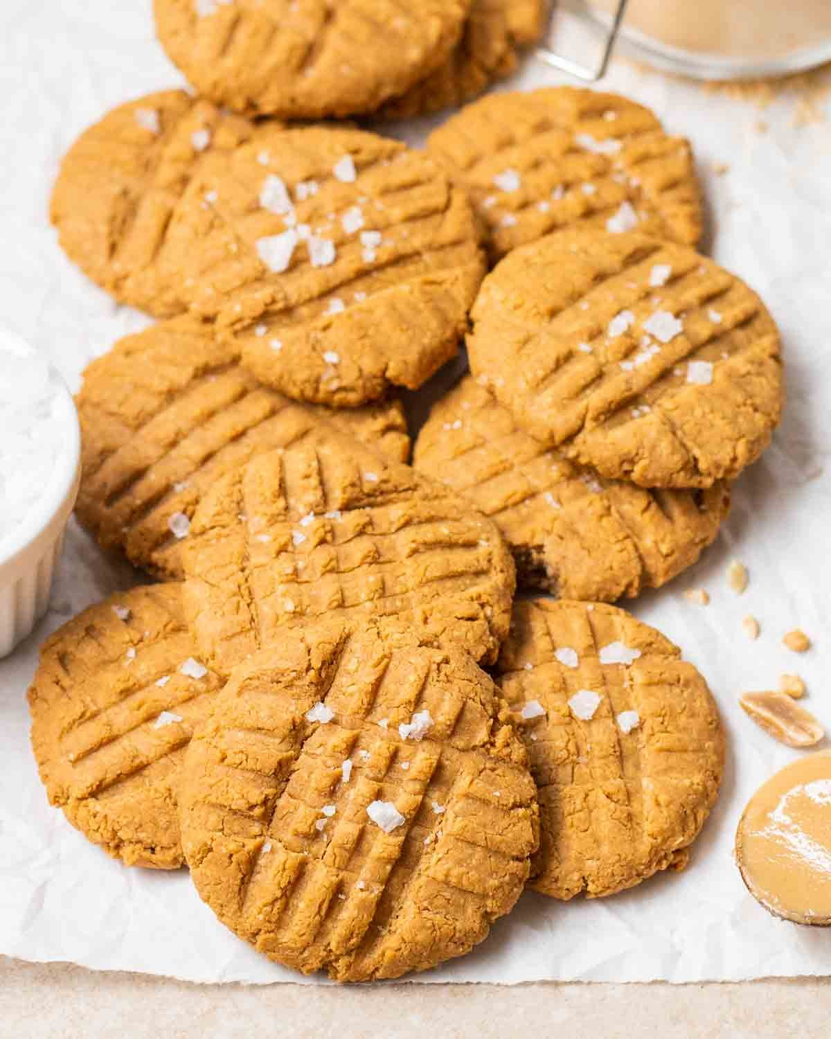 PB2 cookies arranged on a parchment paper topped with sea salt flakes.