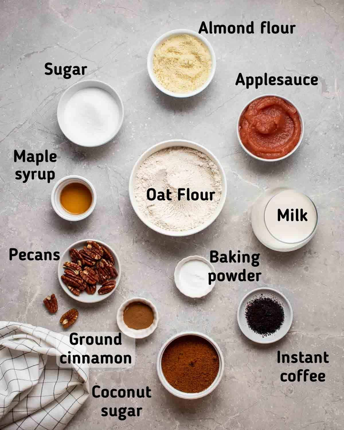 Ingredients needed like oat flour, applesauce, coconut sugar, milk, coffee granules and others on grey background.