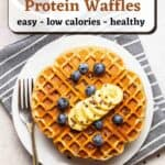 Waffles on a white plate topped with fruits and served with a fork with text overlay.