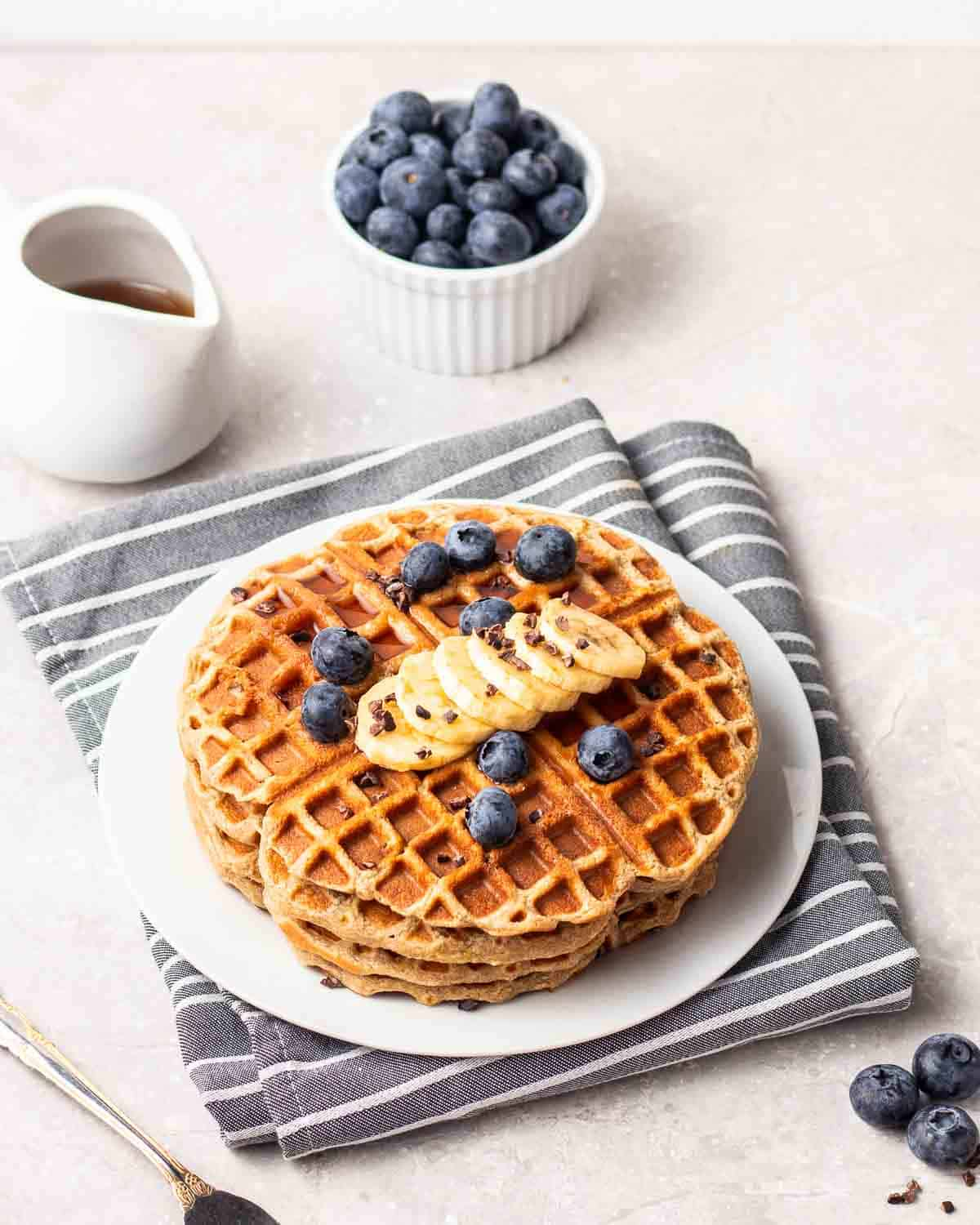 Stack of waffles on a white plate with a bowl of blueberries and maple syrup in the background.