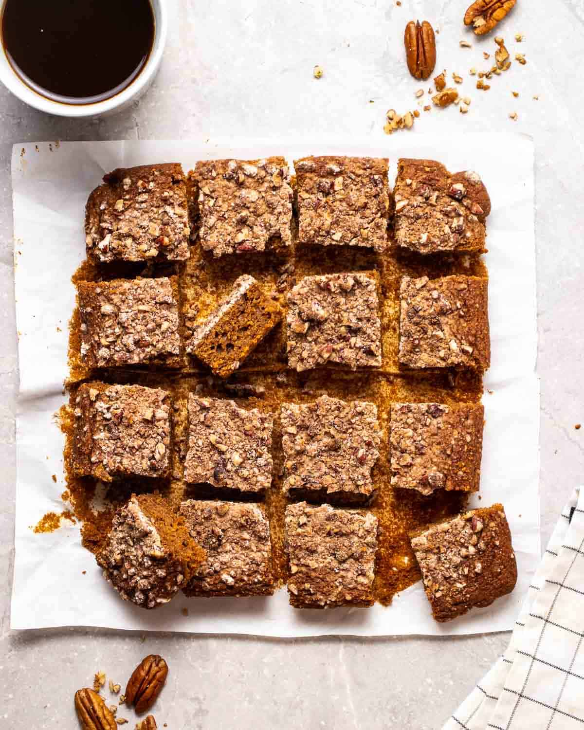 A tray of sliced coffee cake on parchment paper with a cup of coffee and pecans in the background.
