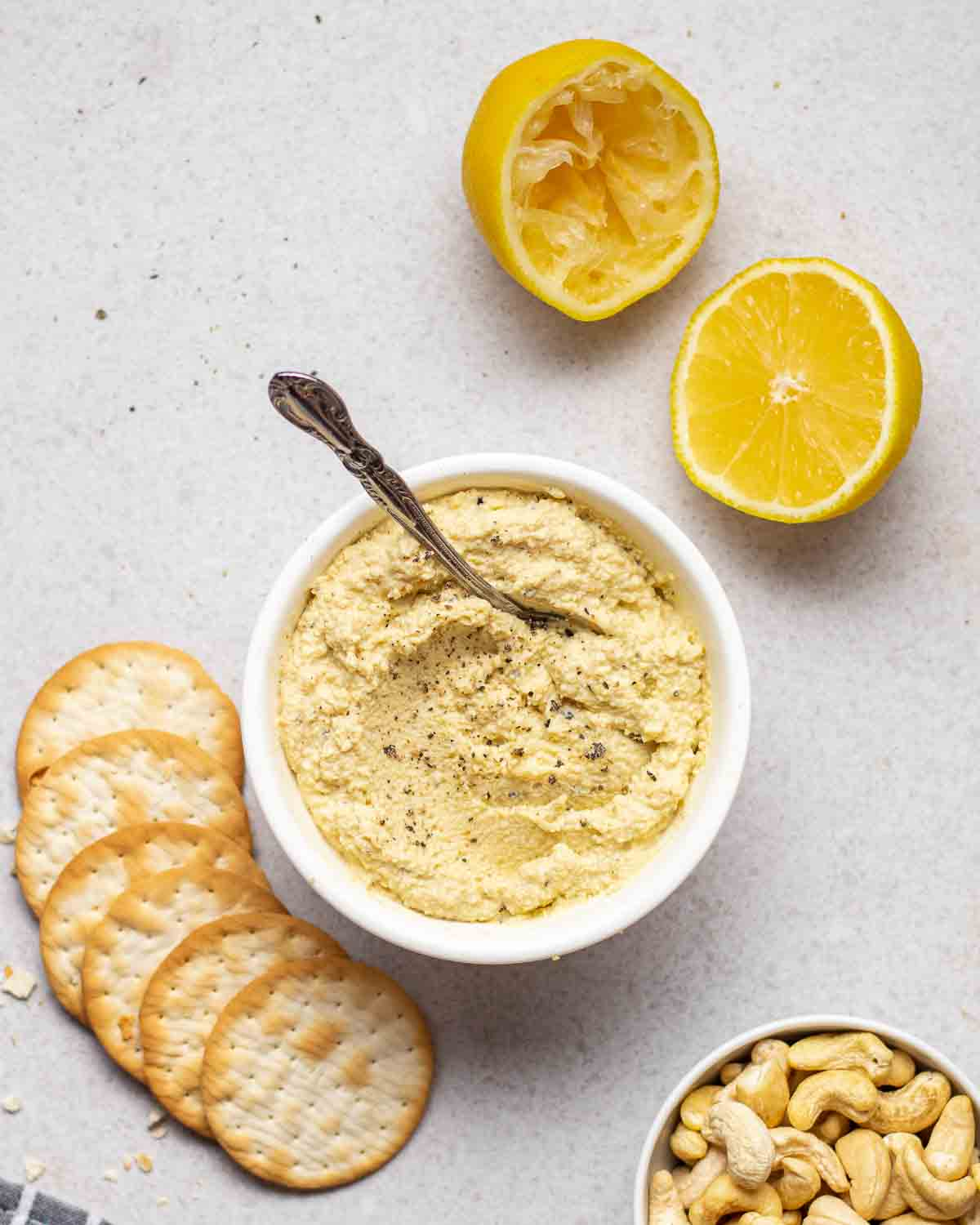 A bowl of dairy-free ricotta with a spoon. There lemon halves, crackers and bowl filled with cashews beside.