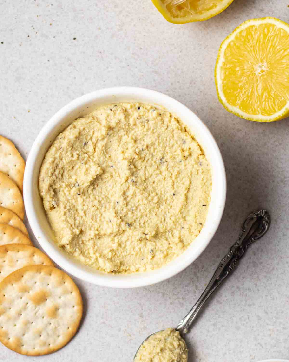 A bowl of tofu cashew ricotta with a spoonful of ricotta, crackers and lemon halves beside.