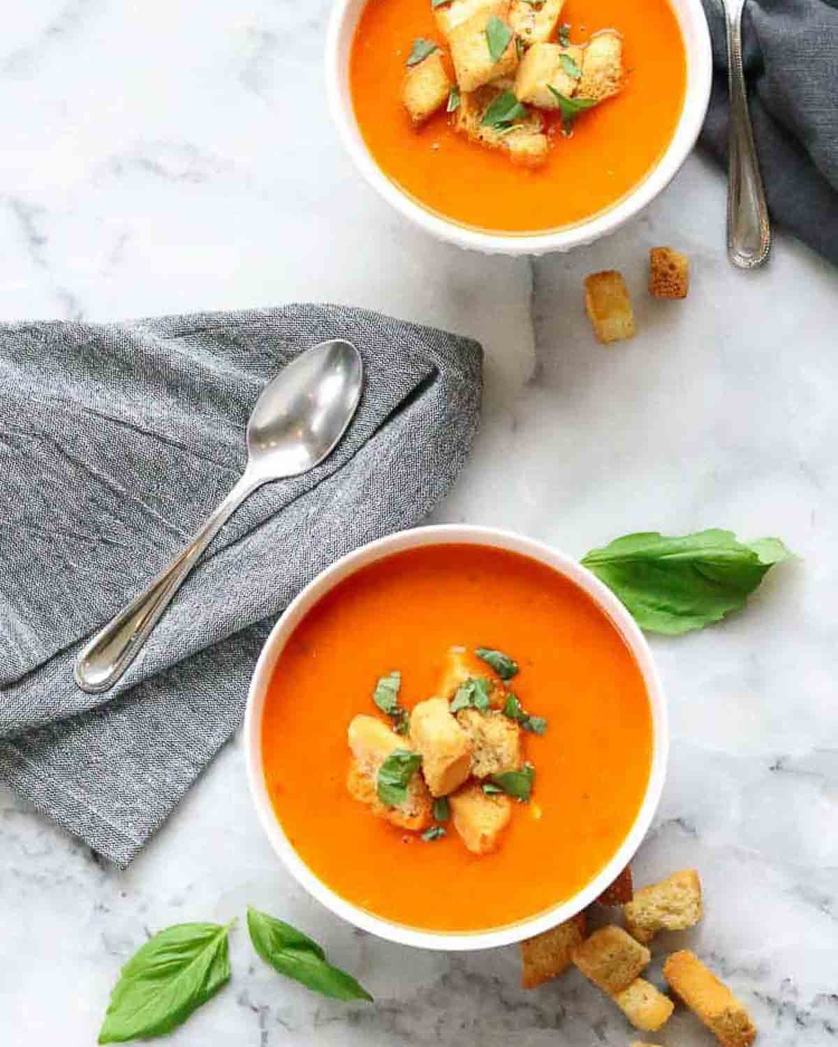 2 bowls of tomato soup topped with croutons and basil. There is a spoon, croutons and basil leaves in the background.