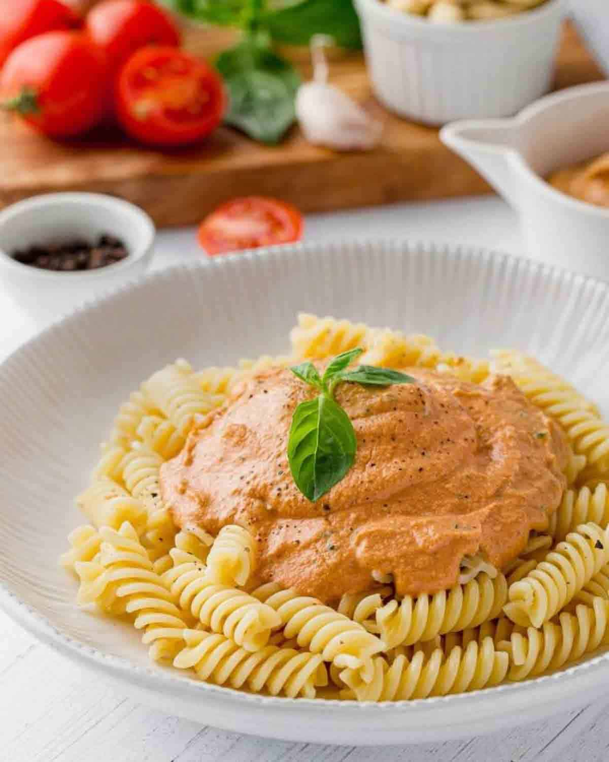 Pasta topped with tomato cream sauce. There is a chopping board with fresh produce in the background.