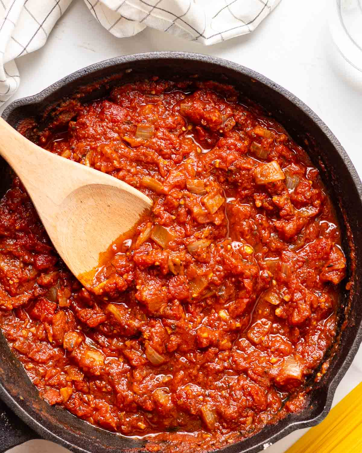 Marinara sauce in a cast iron skillet with a wooden spatula.
