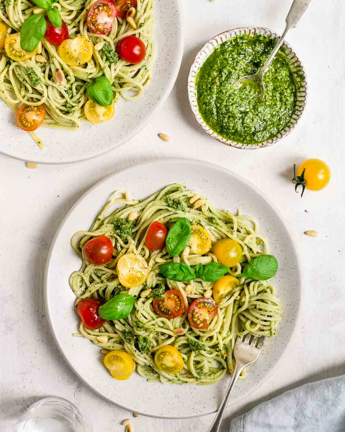 Pesto pasta served in a white plate with fork. There is another plate of pasta and a bowl of pesto beside.