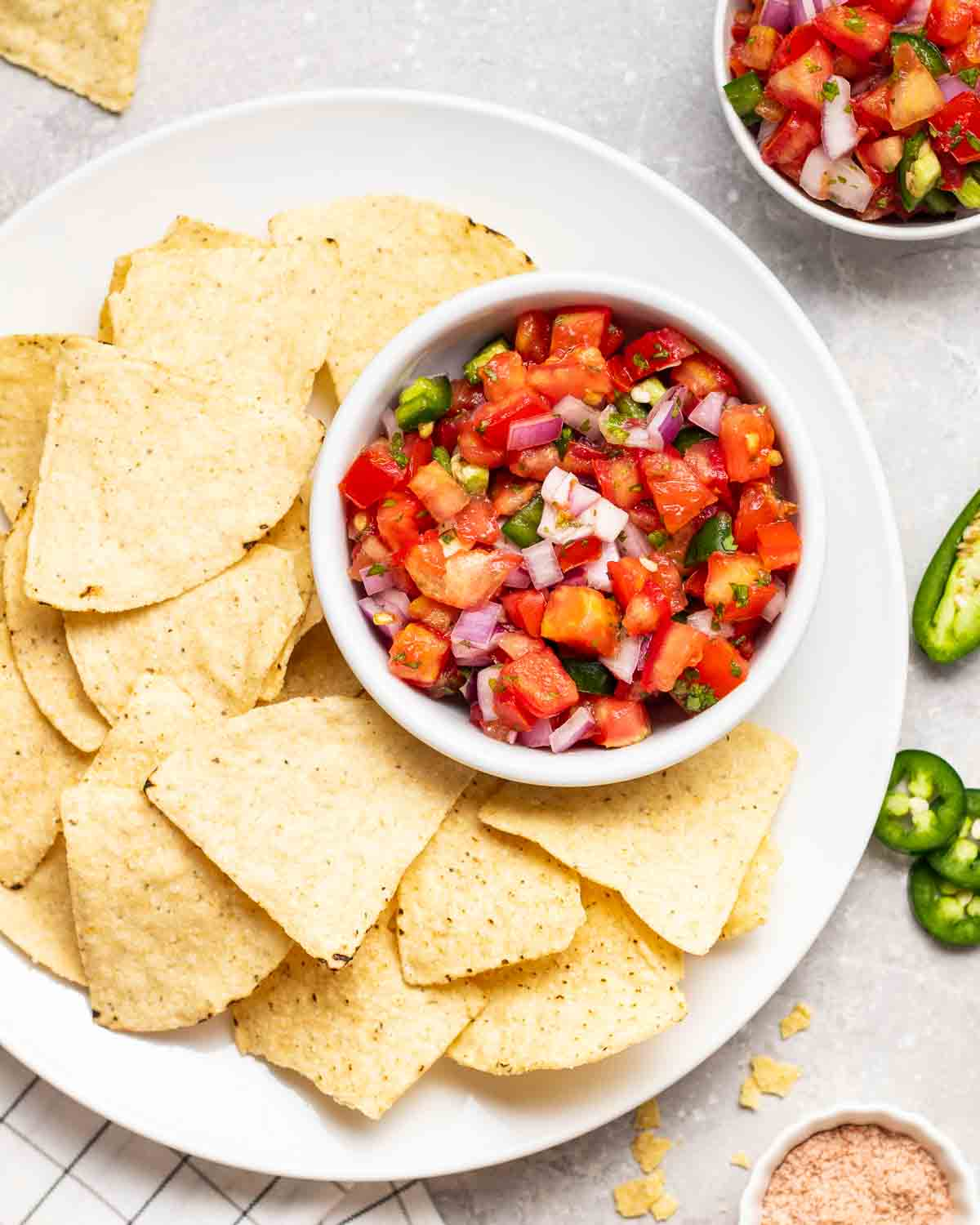 Salsa served with a plate of chips. There are jalapeno peppers and salt in the background.