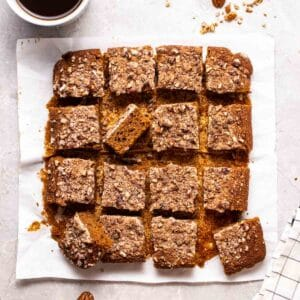 A tray of sliced coffee cake on parchment paper with a cup of coffee beside.