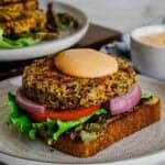 Quinoa patty served on a base of bread and veggies on a plate.