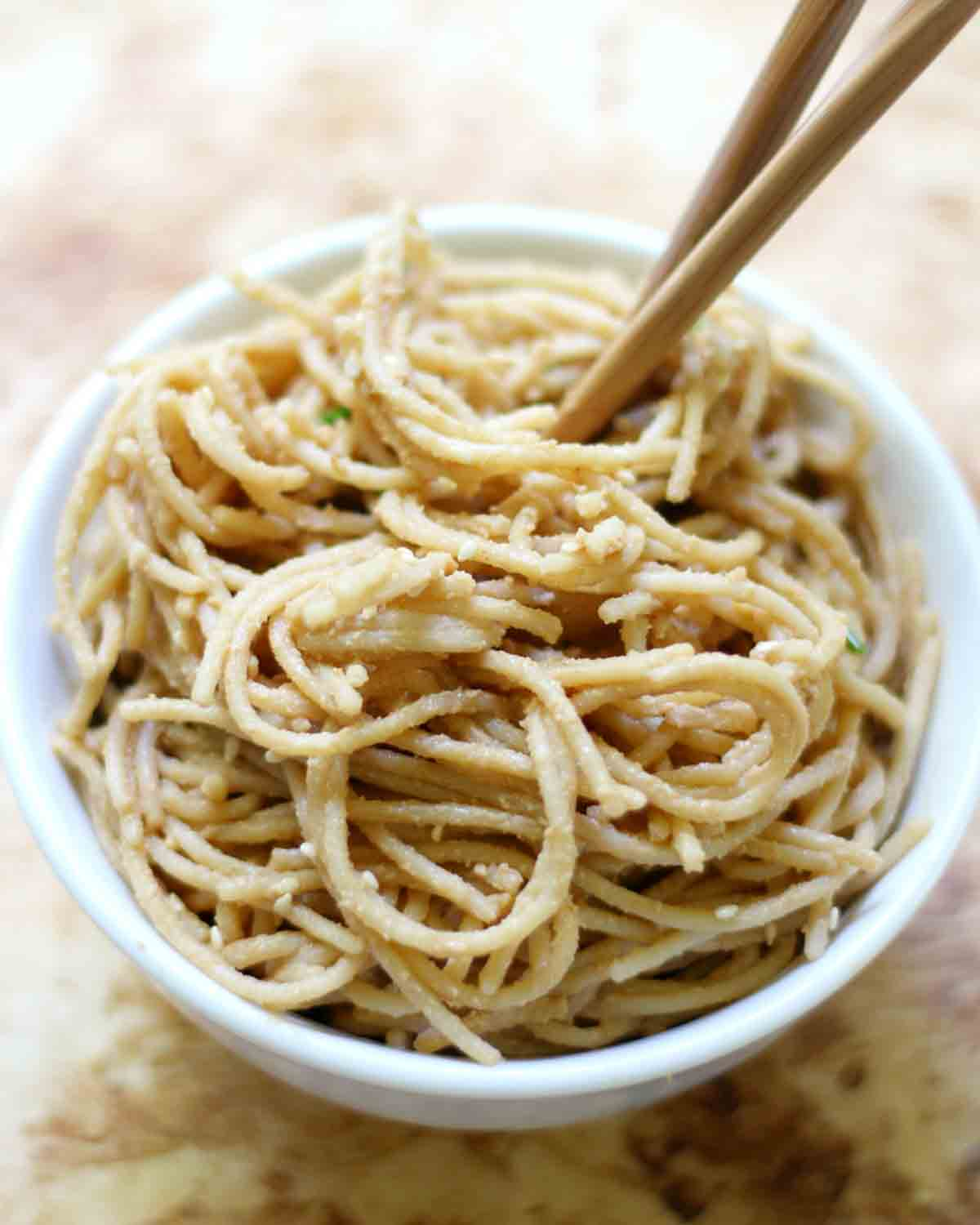 Sesame noodles in a white bowl with a pair of chopsticks.