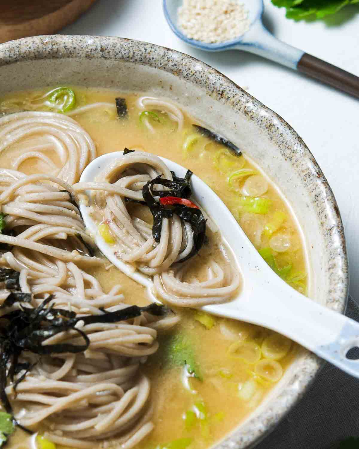 A spoon spooning out some noodles from a bowl of noodle soup.