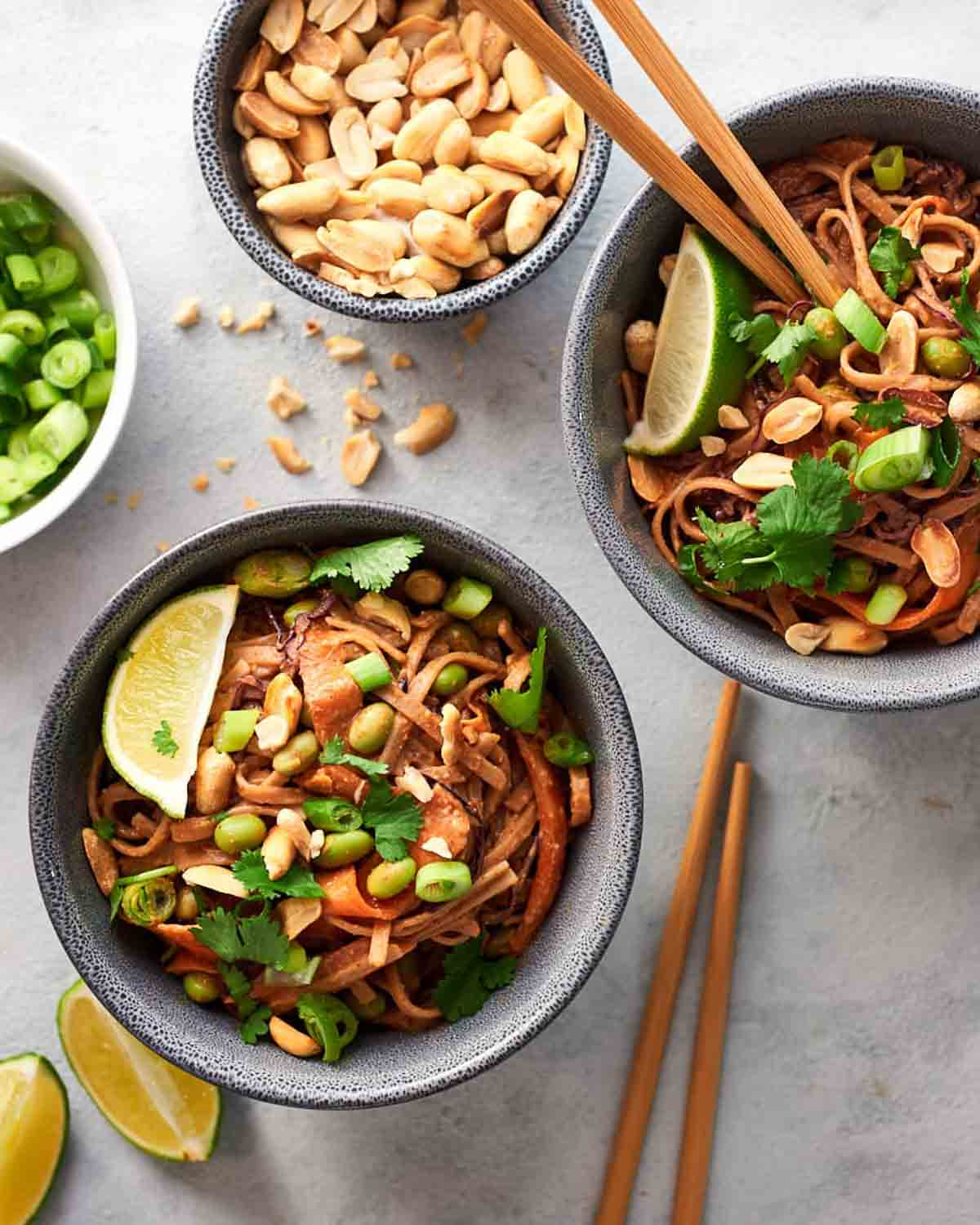 2 bowls of peanut noodles with chopsticks. There is a bowl of peanuts and scallion beside.