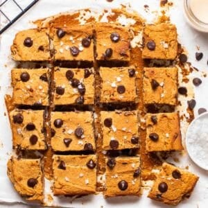 A tray of blondie slices on parchment paper. There is a wire tray, tahini and salt in the background.