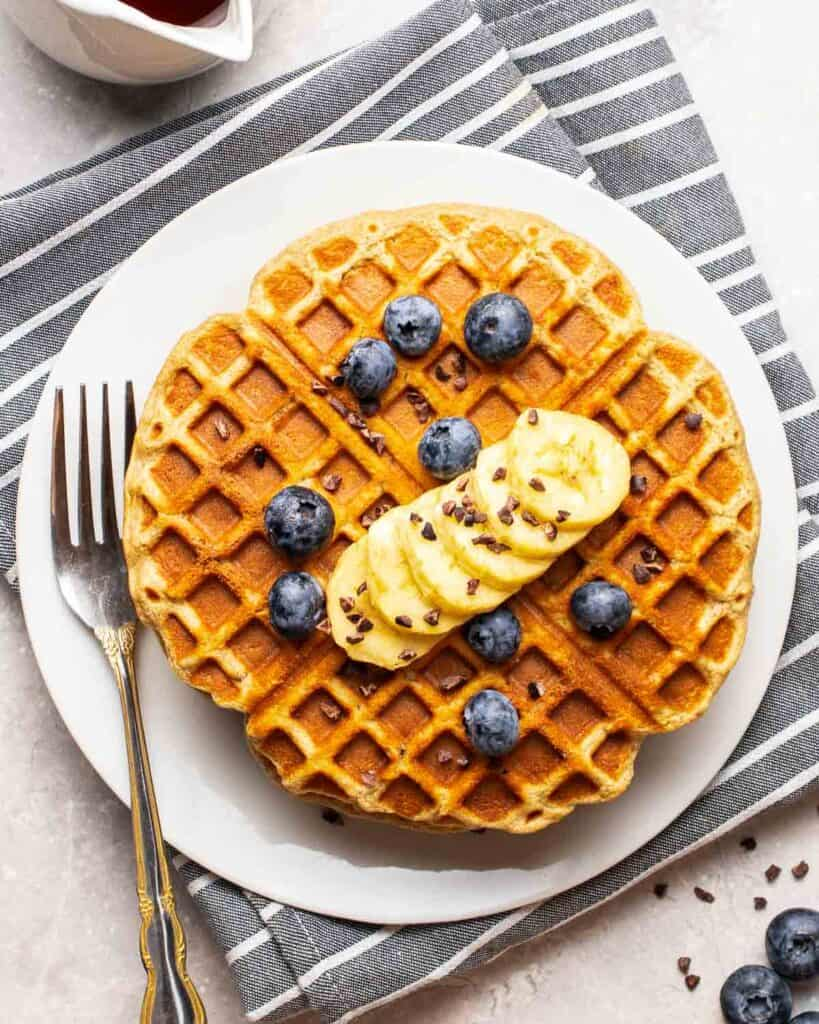 Waffles on a white plate topped with banana slices and blueberries with fork.