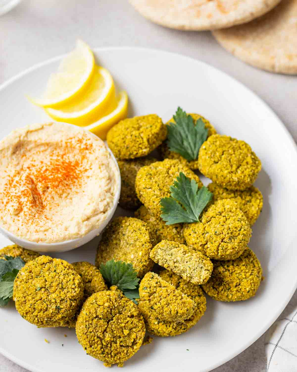 Falafels served with a bowl of hummus on a white plate. There are pitas in the background.
