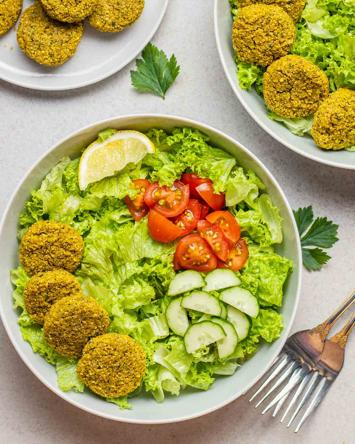 4 falafels served on a bed of greens along with diced tomatoes, cucumbers and a lemon wedge with forks beside.