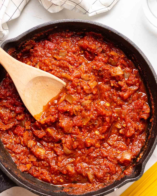 Marinara sauce in black pan with wooden stirrer.