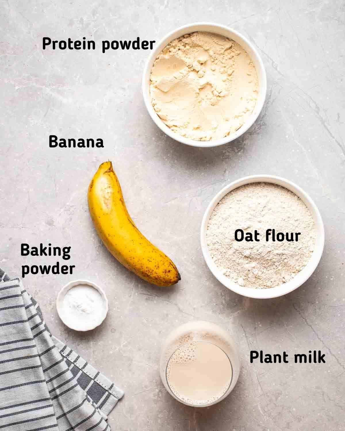 Showing ingredients needed to make waffles like banana, oat flour, baking powder, milk and protein powder.