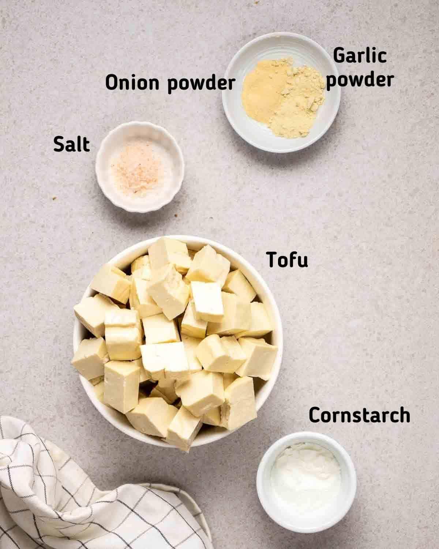 Ingredients needed for tofu like tofu cubes, salt, cornstarch, onion and garlic powder in bowls.