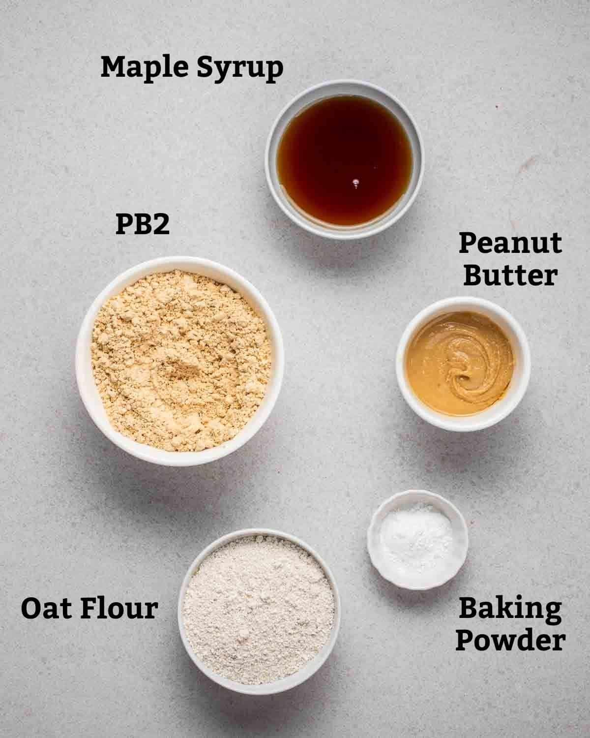 Ingredients needed for PB2 cookies like PB2, peanut butter, maple syrup, flour and baking powder on grey background.