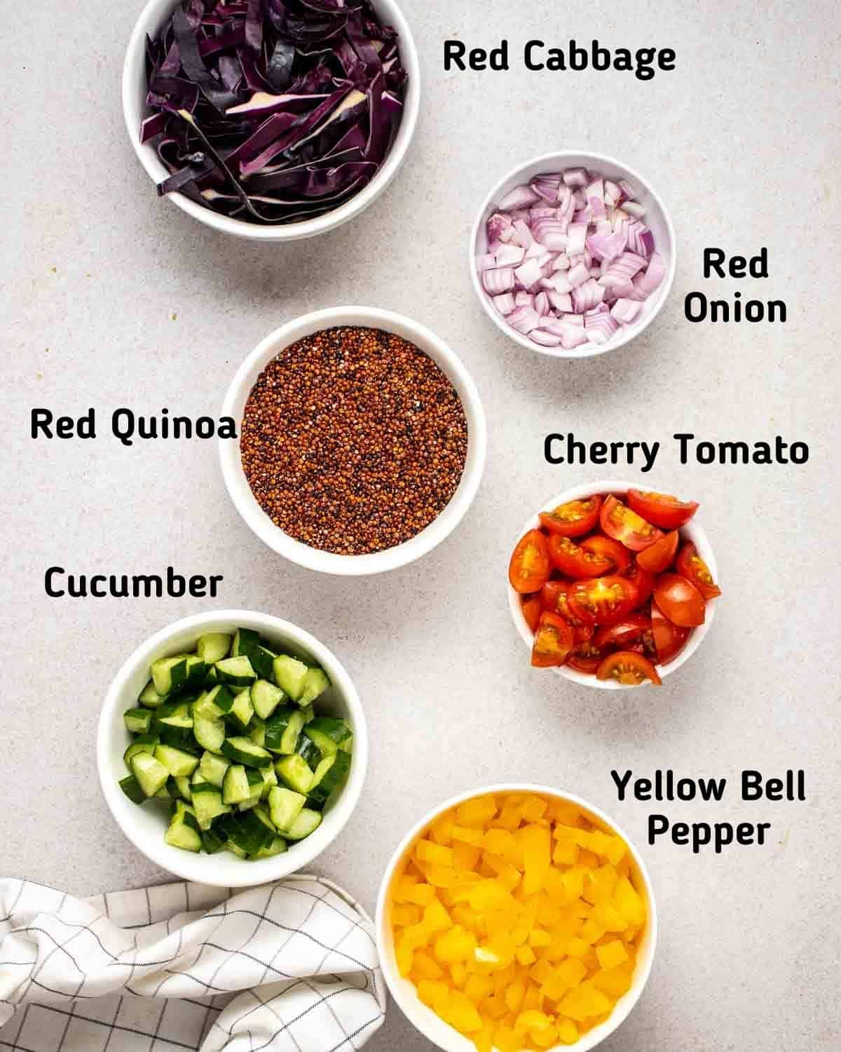 Ingredients needed for salad like quinoa, onion, cabbage, tomato, cucumber and bell pepper on a grey background.