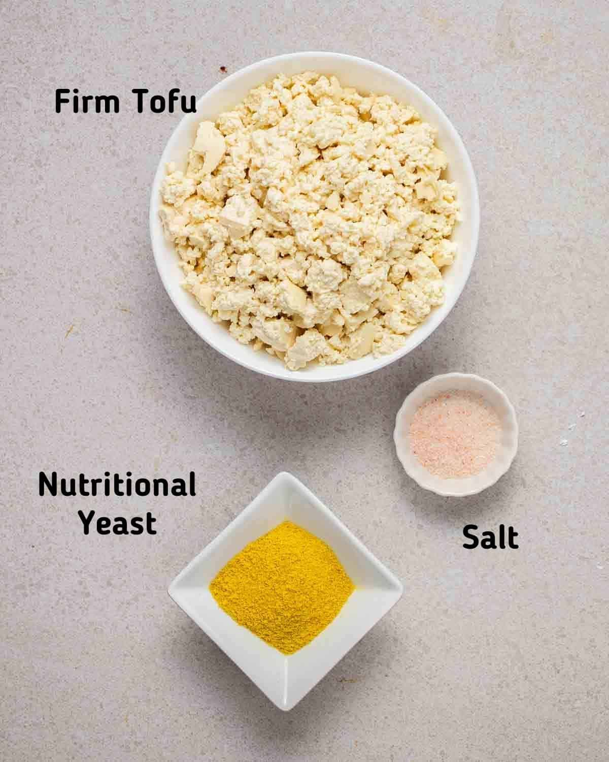 Showing ingredients needed to make scrambled tofu  like tofu, nutritional yeast and salt on a grey background.