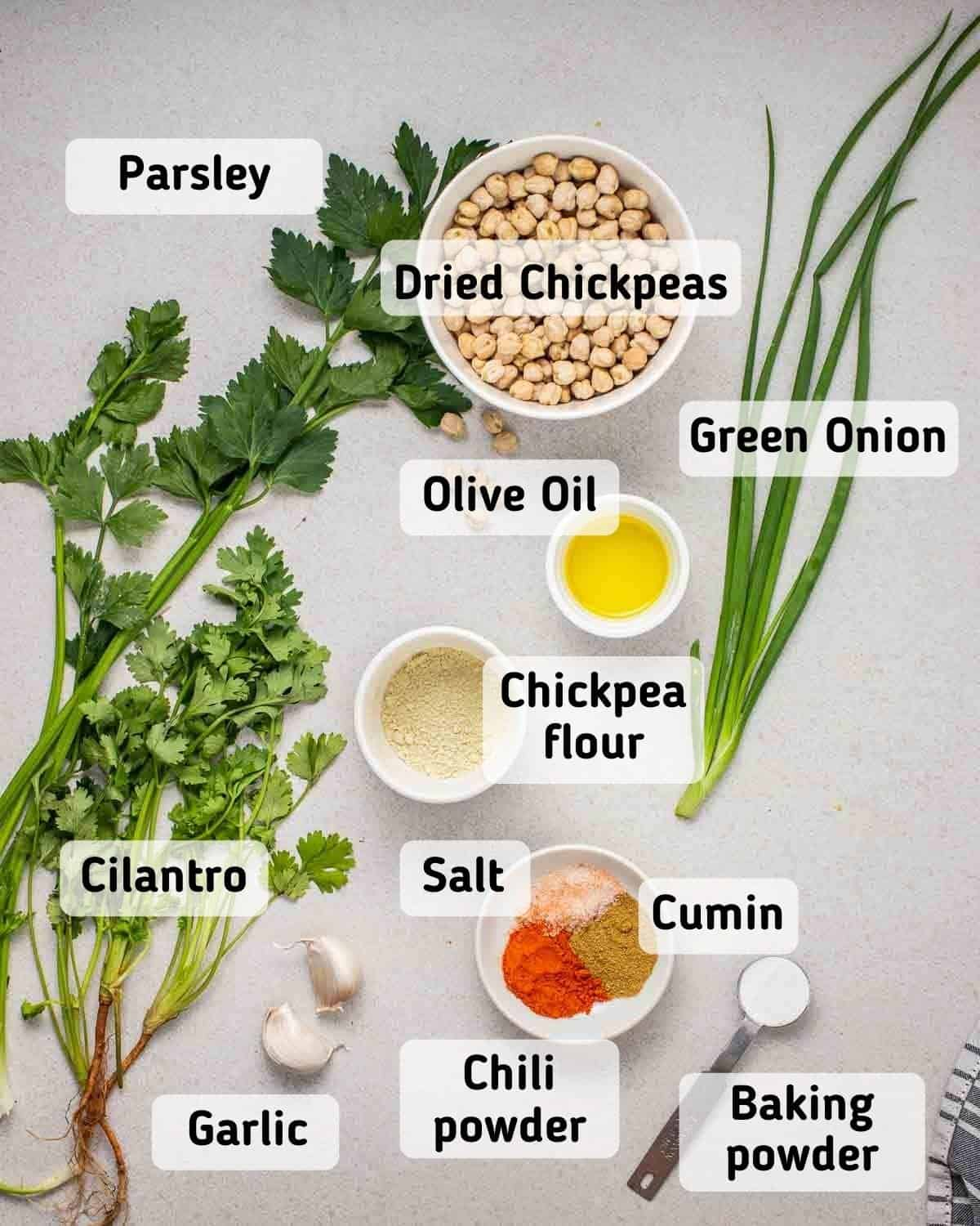 Ingredients needed for falafels like chickpeas olive oil, chickpea flour, baking powder, herbs and spices on grey background.